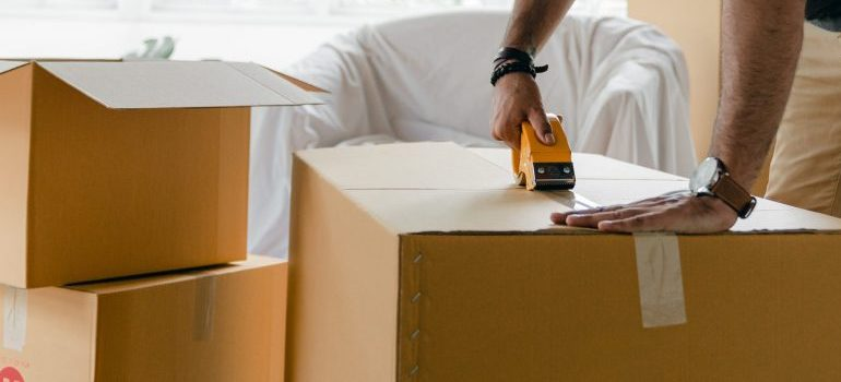 person packing and sealing up cardboard boxes