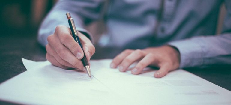 person signing a moving insurance contract