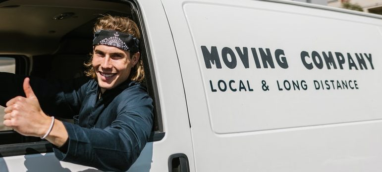 A guy sitting inside a moving truck